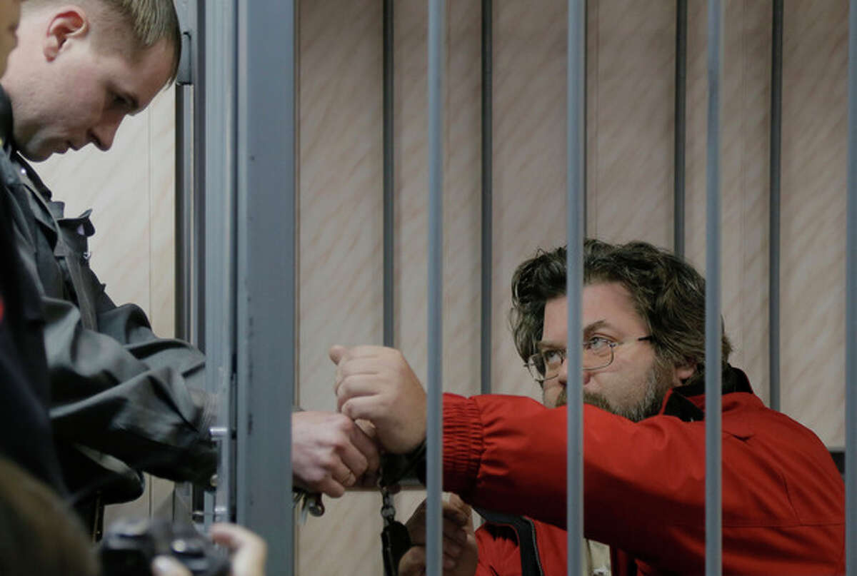 A police officer removes the handcuffs from Greenpeace activist Roman Dolgov, right, in a court room in Murmansk, Russia, on Thursday, Sept. 26, 2013. A Russian court on Thursday jailed Greenpeace arctic project coordinator Roman Dolgov, who was part of the 30-member Greenpeace team protesting near an oil platform last week. Two members of the group were detained Sept. 18 in their attempt to scale the Russian Arctic platform. The Coast Guard seized Greenpeace's ship the next day and towed it with the 30 activists aboard, to Murmansk. The activists are being investigated for piracy. (AP Photo/Efrem Lukatsky)