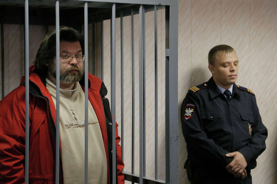 A police officer guards a cage with Greenpeace activist Roman Dolgov, left, in a court room in Murmansk, Russia, on Thursday, Sept. 26, 2013. A Russian court on Thursday jailed Greenpeace arctic project coordinator Roman Dolgov, who was part of the 30-member Greenpeace team protesting near an oil platform last week. Two members of the group were detained Sept. 18 in their attempt to scale the Russian Arctic platform. The Coast Guard seized Greenpeace's ship the next day and towed it with the 30 activists aboard, to Murmansk. The activists are being investigated for piracy. (AP Photo/Efrem Lukatsky) / AP