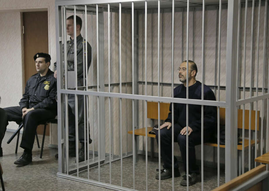 Greenpeace activist Dmitry Litvinov, a US and Swiss citizen, sits in a cage in a court room in Murmansk, Russia, on Thursday, Sept. 26, 2013. A Russian court on Thursday jailed Greenpeace activist Dmitry Litvinov, who was part of the 30-member Greenpeace team protesting near an oil platform last week. The Coast Guard disrupted an attempt by Greenpeace activists on Sept. 18 to scale the Russian Arctic platform. Russian authorities seized Greenpeace's ship the next day and towed it with the 30 activists aboard to Murmansk. The activists are being investigated for piracy. (AP Photo/Efrem Lukatsky)