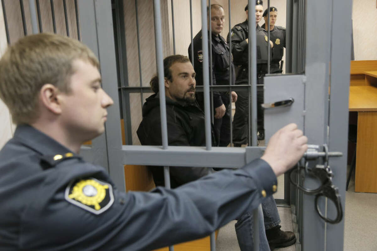 Police officers guard a cage with Greenpeace activist Pisanu Francesco Pierre, center, of France in a court room in Murmansk, Russia, on Thursday, Sept. 26, 2013. A Russian court on Thursday jailed a photographer and two Greenpeace activists who were part of the 30-member Greenpeace team protesting near an oil platform in the Arctic last week. The Coast Guard disrupted an attempt by Greenpeace activists on Sept. 18 to scale the Russian Arctic platform. Russian authorities seized Greenpeace's ship the next day and towed it with the 30 activists aboard to Murmansk. The activists are being investigated for piracy. (AP Photo/Efrem Lukatsky)