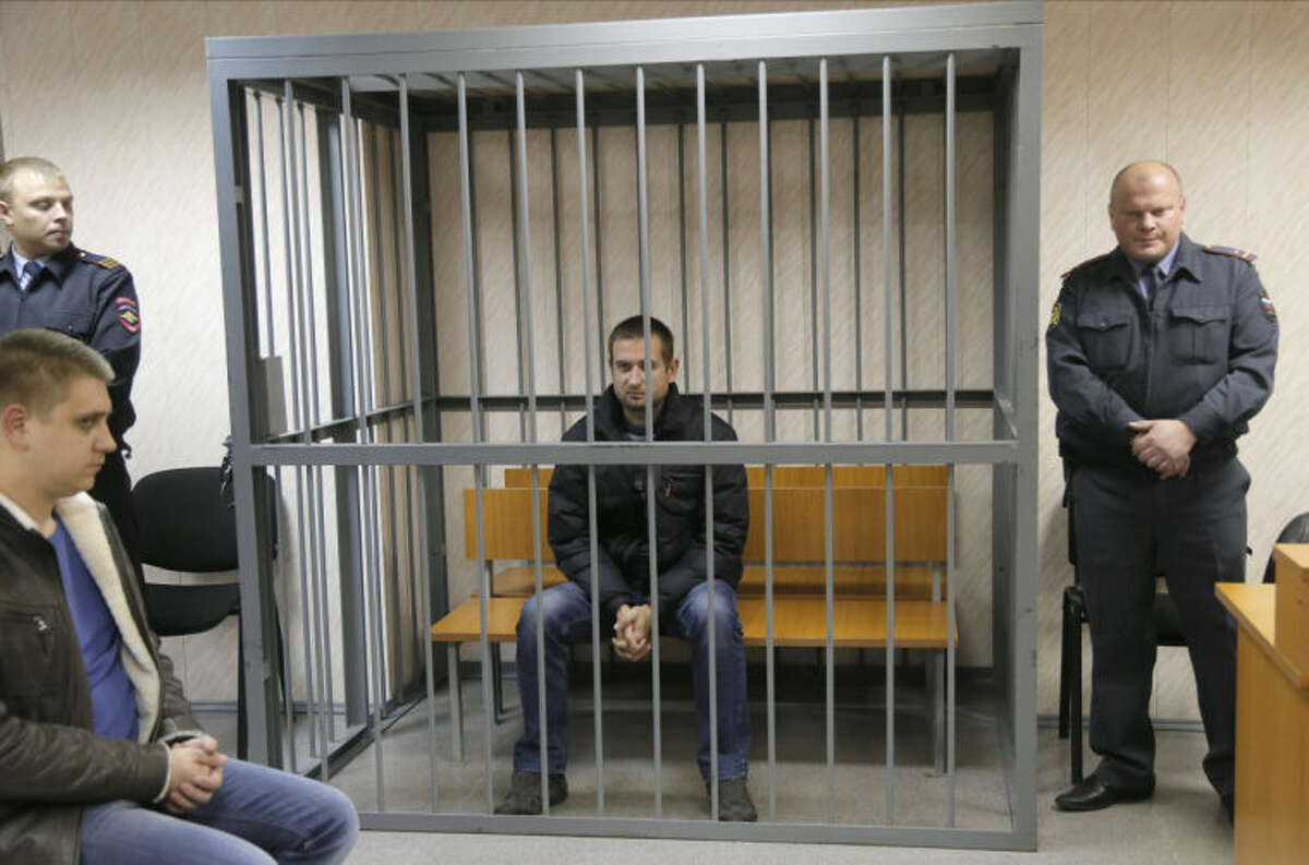 A police officers guards a cage with Greenpeace activist Ruslan Yakushev of Ukraine in a court room in Murmansk, Russia, on Thursday, Sept. 26, 2013. A Russian court on Thursday jailed the activist who was part of the 30-member Greenpeace team protesting near an oil platform last week. Two members of the group were detained Sept. 18 in their attempt to scale the Russian Arctic platform. The Coast Guard seized Greenpeace's ship the next day and towed it with the 30 activists aboard, to Murmansk. The activists are being investigated for piracy. (AP Photo/Efrem Lukatsky)