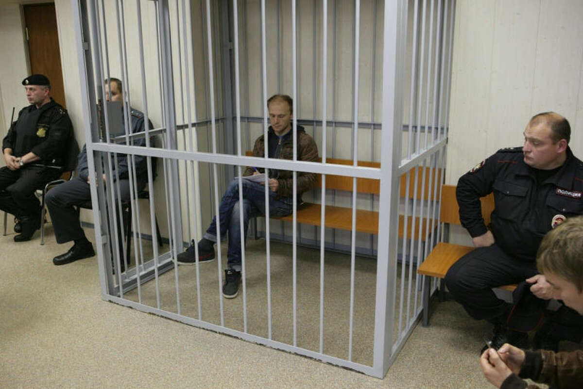 In this photo dated Thursday Sept. 26, 2013 and released by environmental activist group Greenpeace, photographer Denis Sinyakov, center, sits in a cage in a court room in Murmansk, Russia. A Russian court on Thursday jailed two of the 30-member Greenpeace team protesting near an oil platform last week. Two members of the group were detained Sept. 18 in their attempt to scale the Russian Arctic platform. The Coast Guard seized Greenpeace's ship the next day and towed it with the 30 activists aboard, to Murmansk. The activists are being investigated for piracy. (AP Photo/Greenpeace)