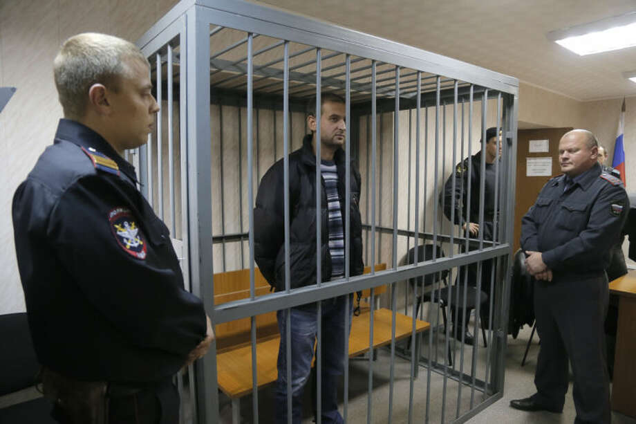 A police officers guards a cage with Greenpeace activist Ruslan Yakushev of Ukraine in a court room in Murmansk, Russia, Thursday, Sept. 26, 2013. A Russian court on Thursday jailed the activist who was part of the 30-member Greenpeace team protesting near an oil platform last week. Two members of the group were detained Sept. 18 in their attempt to scale the Russian Arctic platform. The Coast Guard seized Greenpeace's ship the next day and towed it with the 30 activists aboard, to Murmansk. The activists are being investigated for piracy. (AP Photo/Efrem Lukatsky)