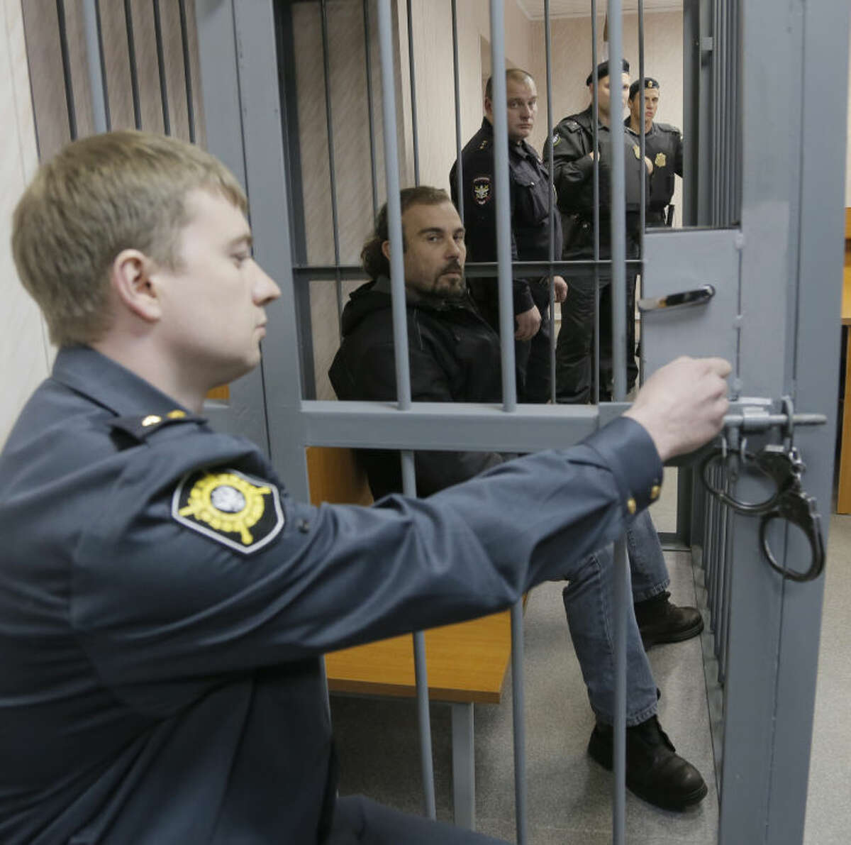 Police officers guard a cage with Greenpeace activist Pisanu Francesco Pierre, center, of France in a court room in Murmansk, Russia, Thursday, Sept. 26, 2013. A Russian court on Thursday jailed Greenpeace activist Pisanu Francesco Pierre who was part of the 30-member Greenpeace team protesting near an oil platform last week. The Coast Guard disrupted an attempt by Greenpeace activists on Sept. 18 to scale the Russian Arctic platform. Russian authorities seized Greenpeace's ship the next day and towed it with the 30 activists aboard to Murmansk. The activists are being investigated for piracy. (AP Photo/Efrem Lukatsky)