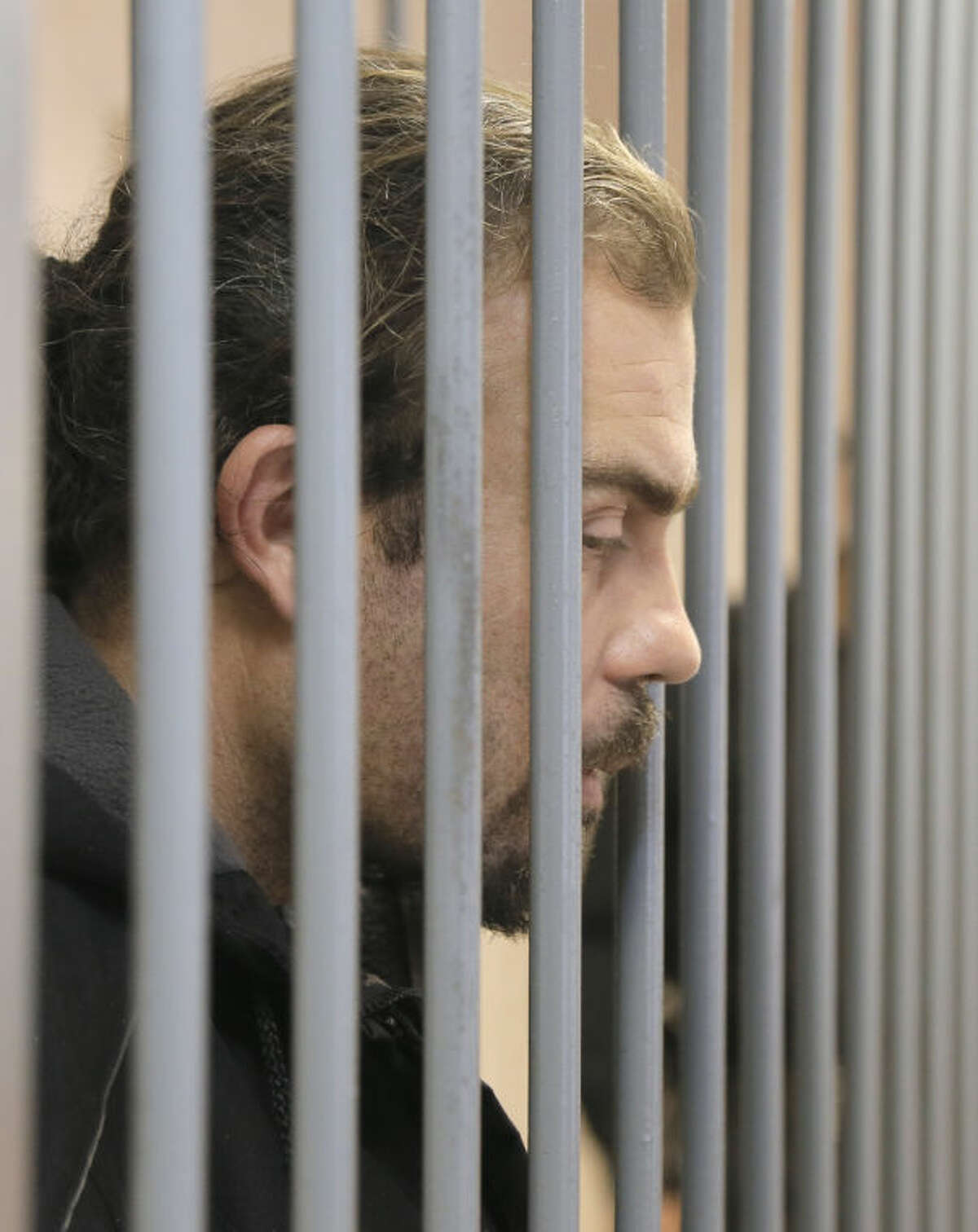 Greenpeace activist Pisanu Francesco Pierre of France sits in a cage in a court room in Murmansk, Russia, on Thursday, Sept. 26, 2013. A Russian court on Thursday jailed a photographer and two Greenpeace activists who were part of the 30-member Greenpeace team protesting near an oil platform in the Arctic last week. The Coast Guard disrupted an attempt by Greenpeace activists on Sept. 18 to scale the Russian Arctic platform. Russian authorities seized Greenpeace's ship the next day and towed it with the 30 activists aboard to Murmansk. The activists are being investigated for piracy. (AP Photo/Efrem Lukatsky)