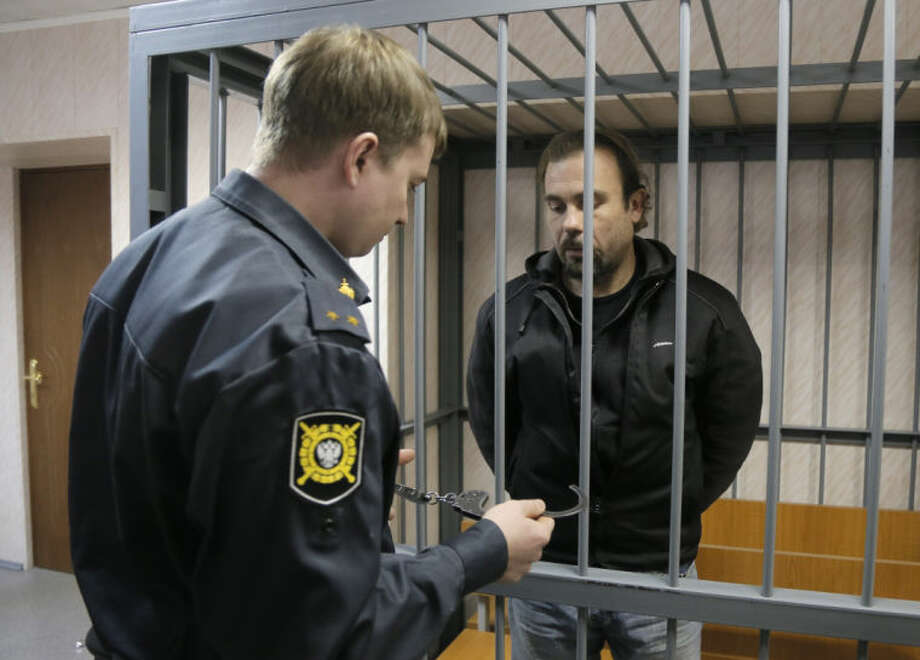 A police officer guards a cage with Greenpeace activist Pisanu Francesco Pierre of France in a court room in Murmansk, Russia, on Thursday, Sept. 26, 2013. A Russian court on Thursday jailed a photographer and two Greenpeace activists who were part of the 30-member Greenpeace team protesting near an oil platform in the Arctic last week. The Coast Guard disrupted an attempt by Greenpeace activists on Sept. 18 to scale the Russian Arctic platform. Russian authorities seized Greenpeace's ship the next day and towed it with the 30 activists aboard to Murmansk. The activists are being investigated for piracy. (AP Photo/Efrem Lukatsky)