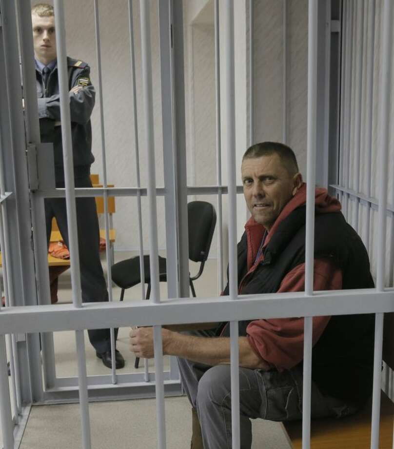 "Jonathon Beauchamp of New Zealand, a mechanic on the Greenpeace ship ""Arctic Sunrise"" sits in a defendants' cage in a court room in Murmansk, Russia, Thursday, Sept. 26, 2013. Beauchamp was one of the 30-member team who took part in a Greenpeace protest near an oil platform in the Arctic last week. A Russian court on Thursday sanctioned a two-month jail term for Jonathon Beauchamp along with some other activists. (AP Photo/Efrem Lukatsky)"