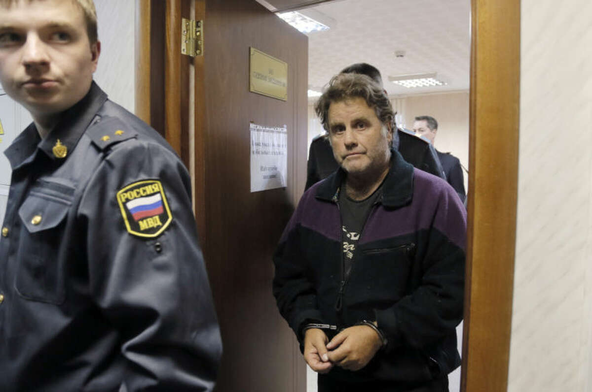 A police officers guards the US captain of the Greenpeace ship 'Arctic Sunrise', Peter Willcox in a court room in Murmansk, Russia, on Thursday, Sept. 26, 2013. A Russian court on Thursday jailed Peter Willcox who was captain of the of Greenpeace ship 'Arctic Sunrise' and member Greenpeace team protesting near an oil platform last week. Two members of the group were detained Sept. 18 in their attempt to scale the Russian Arctic platform. The Coast Guard seized Greenpeace's ship the next day and towed it with the 30 activists aboard, to Murmansk. The activists are being investigated for piracy. (AP Photo/Efrem Lukatsky)