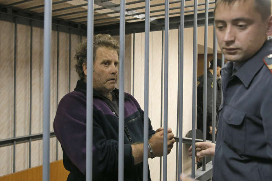A police officer guards the US captain of the Greenpeace ship 'Arctic Sunrise', Peter Willcox in a cage in a court room in Murmansk, Russia, on Thursday, Sept. 26, 2013. A Russian court on Thursday jailed Peter Willcox who was captain of the of Greenpeace ship 'Arctic Sunrise' and member Greenpeace team protesting near an oil platform last week. Two members of the group were detained Sept. 18 in their attempt to scale the Russian Arctic platform. The Coast Guard seized Greenpeace's ship the next day and towed it with the 30 activists aboard, to Murmansk. The activists are being investigated for piracy. (AP Photo/Efrem Lukatsky)