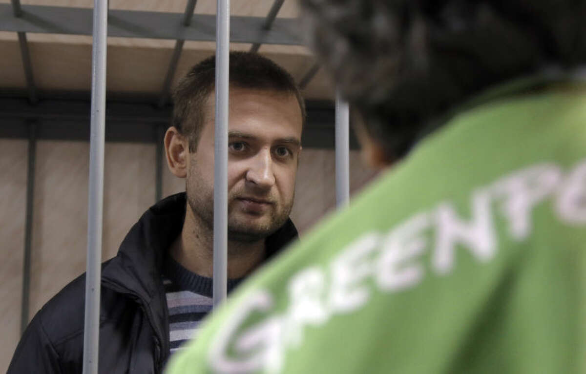 Greenpeace activist Ruslan Yakushev of Ukraine behind bars speaks to a supporter in a court room in Murmansk, Russia, on Thursday, Sept. 26, 2013. A Russian court on Thursday jailed Yakushev who was part of the 30-member team of environmental activists protesting near an oil platform last week. Two members of the group were detained Sept. 18 in their attempt to scale the Russian Arctic platform. The Coast Guard seized Greenpeace's ship the next day and towed it with the 30 activists aboard, to Murmansk. The activists are being investigated for piracy. (AP Photo/Efrem Lukatsky)