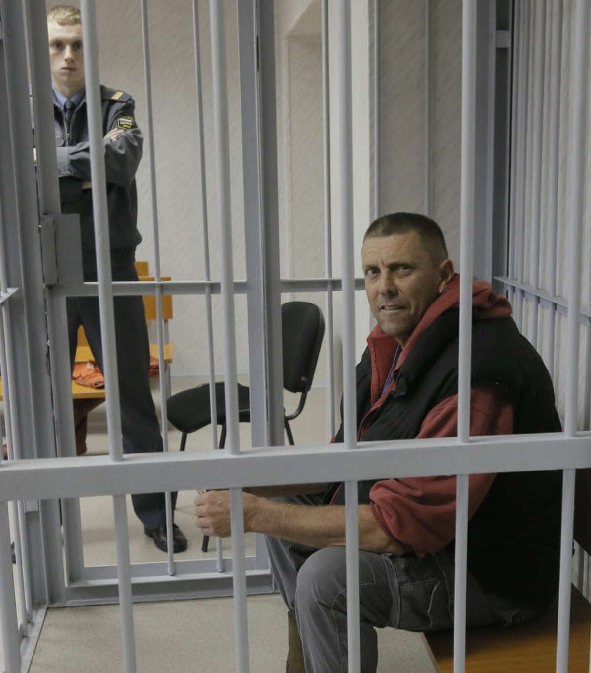 A police officer guards a cage with Greenpeace activist and boat mechanic Jonathon Beauchamp from New Zealand in a court room in Murmansk, Russia, on Thursday, Sept. 26, 2013. A Russian court on Thursday jailed Greenpeace activist Jonathon Beauchamp who was part of the 30-member Greenpeace team protesting near an oil platform last week. The Coast Guard disrupted an attempt by Greenpeace activists on Sept. 18 to scale the Russian Arctic platform. Russian authorities seized Greenpeace's ship the next day and towed it with the 30 activists aboard to Murmansk. The activists are being investigated for piracy. (AP Photo/Efrem Lukatsky)