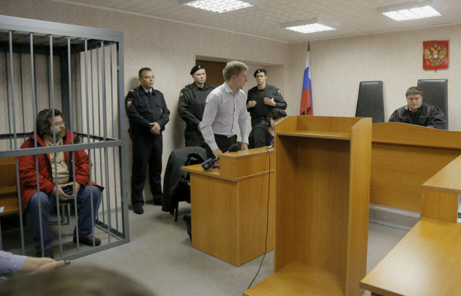 Greenpeace activist Roman Dolgov, left, sits in a cage during a hearing in a court room in Murmansk, Russia, on Thursday, Sept. 26, 2013. A Russian court on Thursday jailed Greenpeace arctic project coordinator Roman Dolgov, who was part of the 30-member Greenpeace team protesting near an oil platform last week. Two members of the group were detained Sept. 18 in their attempt to scale the Russian Arctic platform. The Coast Guard seized Greenpeace's ship the next day and towed it with the 30 activists aboard, to Murmansk. The activists are being investigated for piracy. (AP Photo/Efrem Lukatsky)