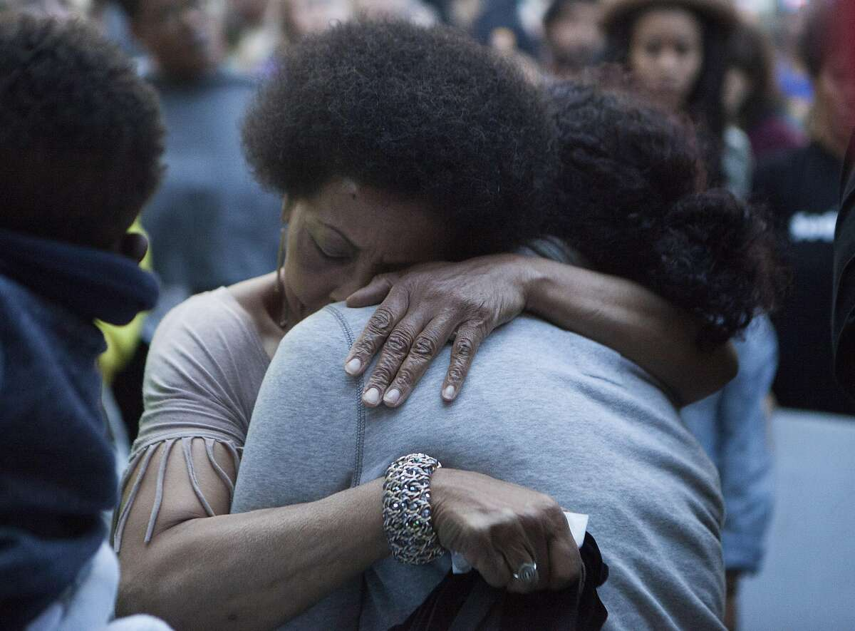 Mattie Scott of San Fransisco hugs friends of Reggina Jefferies on Wednesday, June 15, 2016 in Oakland, California. Jeffries was killed on Tuesday during a broad-daylight shooting.