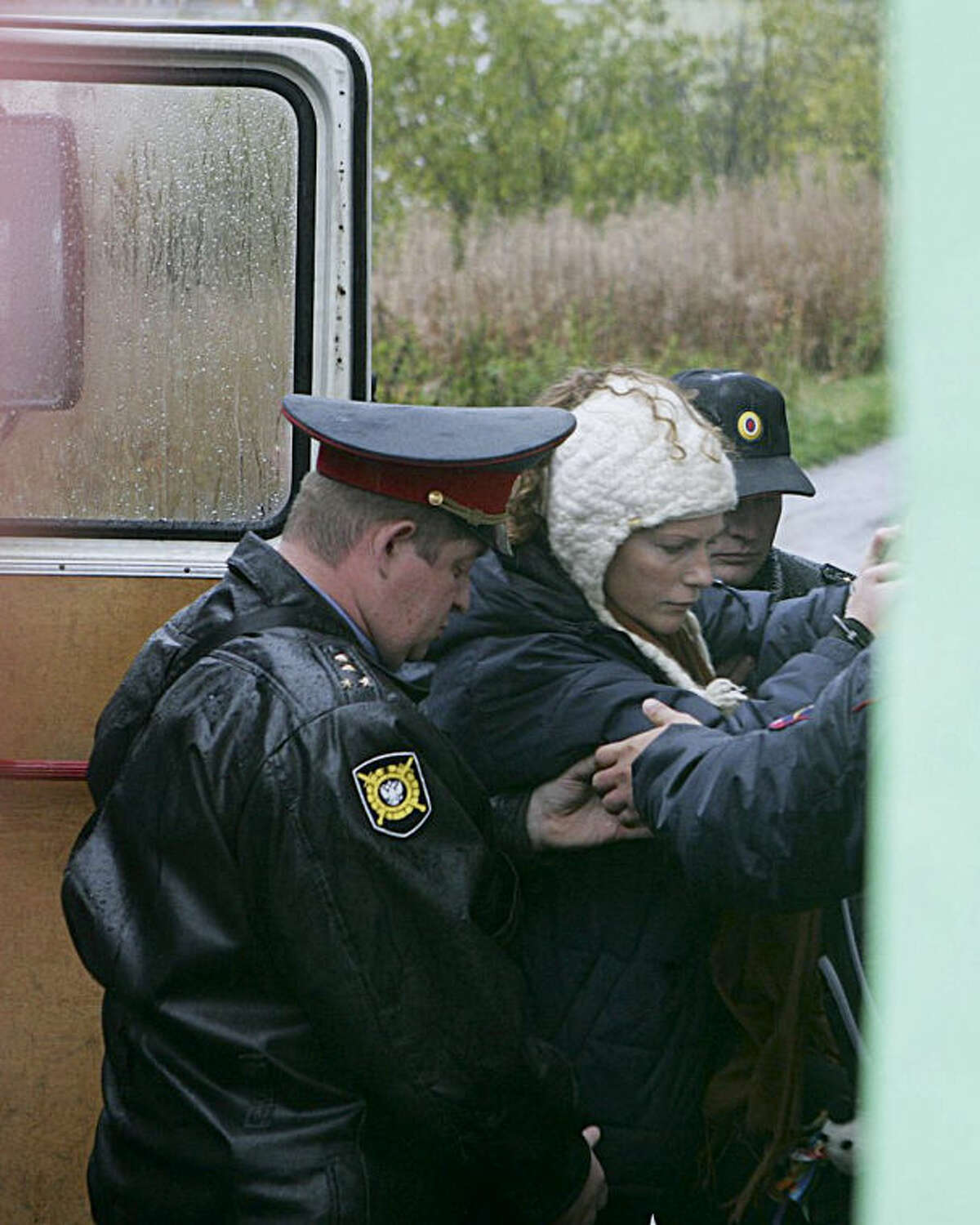 In this photo dated Thursday Sept. 26, 2013 by environmental activist group Greenpeace, Russian police officers escort a Greenpeace activist, no name available, to a court room in Murmansk, Russia. A Russian court on Thursday jailed two of the 30-member Greenpeace team protesting near an oil platform last week. Two members of the group were detained Sept. 18 in their attempt to scale the Russian Arctic platform. The Coast Guard seized Greenpeace's ship the next day and towed it with the 30 activists aboard, to Murmansk. The activists are being investigated for piracy. (AP Photo/Greenpeace)