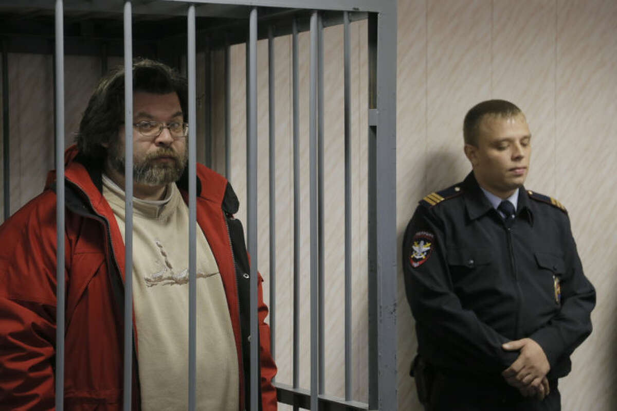 A police officer guards a cage with Greenpeace activist Roman Dolgov, left, in a court room in Murmansk, Russia, on Thursday, Sept. 26, 2013. A Russian court on Thursday jailed Greenpeace arctic project coordinator Roman Dolgov, who was part of the 30-member Greenpeace team protesting near an oil platform last week. Two members of the group were detained Sept. 18 in their attempt to scale the Russian Arctic platform. The Coast Guard seized Greenpeace's ship the next day and towed it with the 30 activists aboard, to Murmansk. The activists are being investigated for piracy. (AP Photo/Efrem Lukatsky)