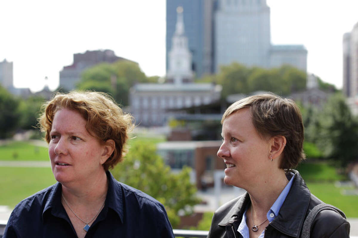 Plaintiffs Cara Palladino and her spouse Isabelle Barker speak with an attorney after a news conference, Thursday, Sept. 26, 2013, near Independence Hall in Philadelphia. Cara Palladino and Isabelle Barker, who were legally married in Massachusetts and moved to Pennsylvania, filed a federal lawsuit Thursday aiming to overturn the 1996 amendment to a state law stating same-sex marriages, including those recorded elsewhere, are not legal within the state.(AP Photo/Matt Rourke)