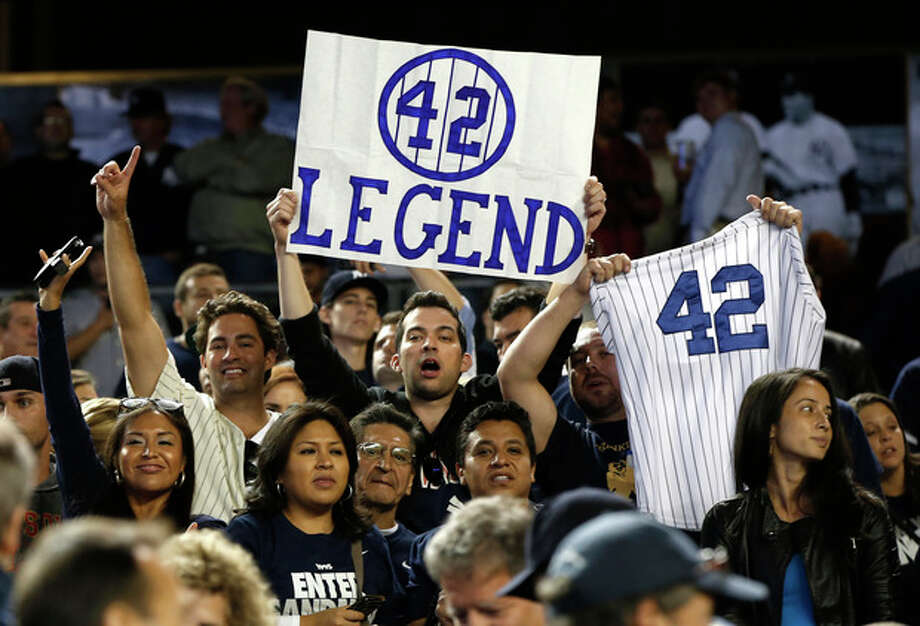 Fans of New York Yankees relief pitcher Mariano Rivera (42) hold signs after Rivera's final appearance at a baseball game at Yankee Stadium, Thursday, Sept. 26, 2013, in New York. (AP Photo/Kathy Willens) / AP
