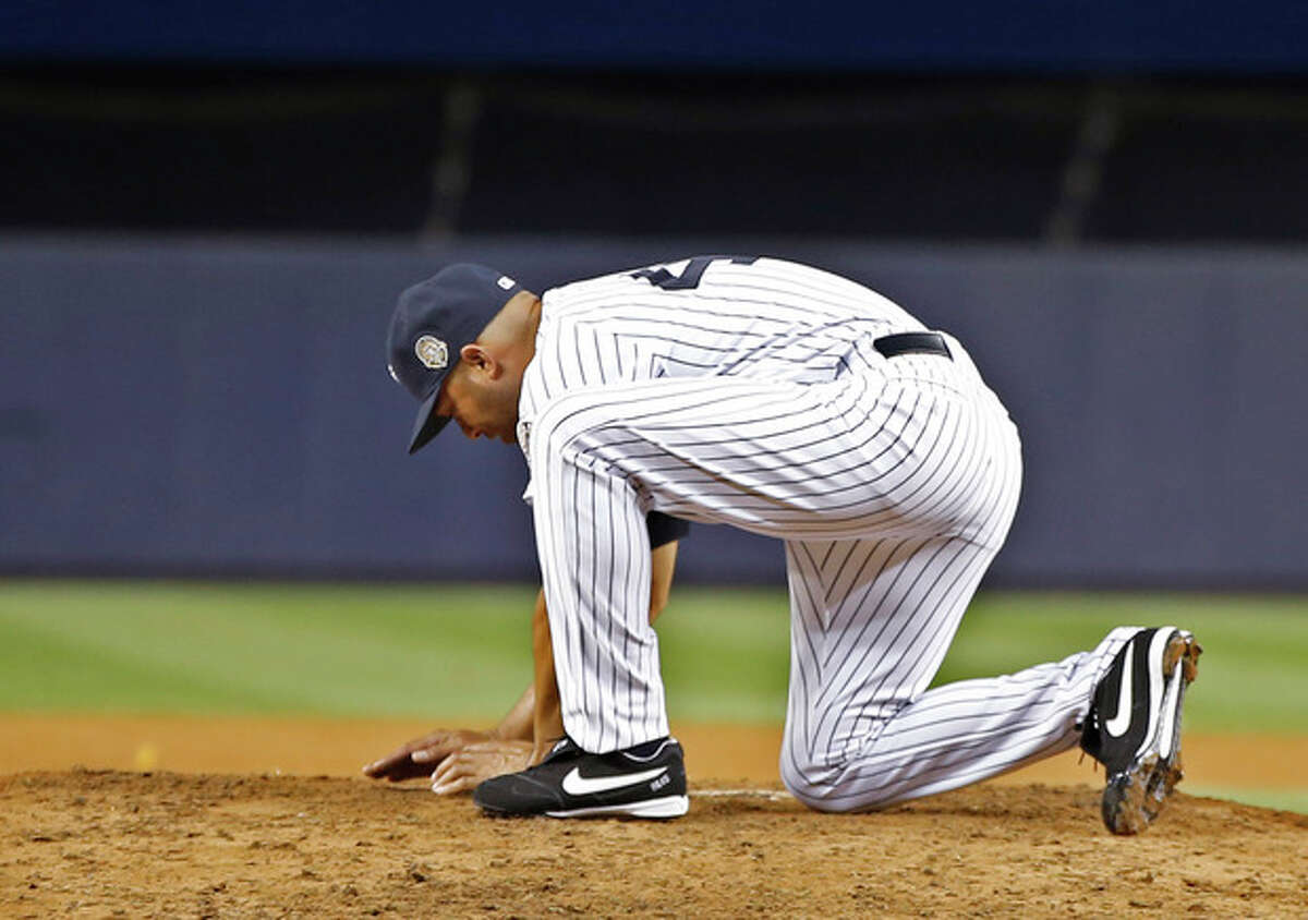 New York Yankees relief pitcher Mariano Rivera gathers dirt from the mound after his final appearance in a baseball game at Yankee Stadium, Thursday, Sept. 26, 2013, in New York. The Yankees defeated the Tampa Bay Rays 4-0. (AP Photo/Kathy Willens)