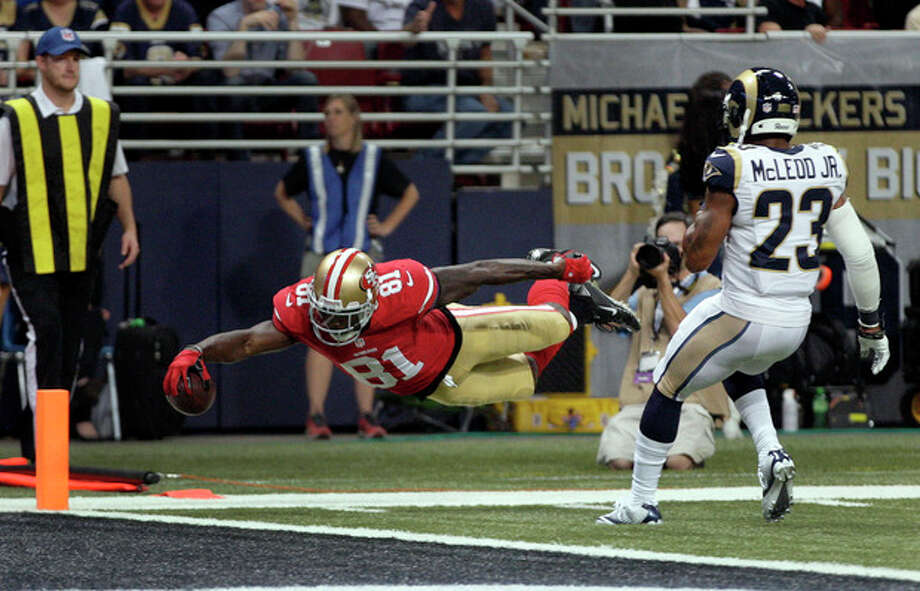 San Francisco 49ers wide receiver Anquan Boldin, left, dives into the end zone with a 20-yard touchdown reception as St. Louis Rams safety Rodney McLeod watches during the second quarter of an NFL football game Thursday, Sept. 26, 2013, in St. Louis. (AP Photo/Tom Gannam) / FR45452 AP