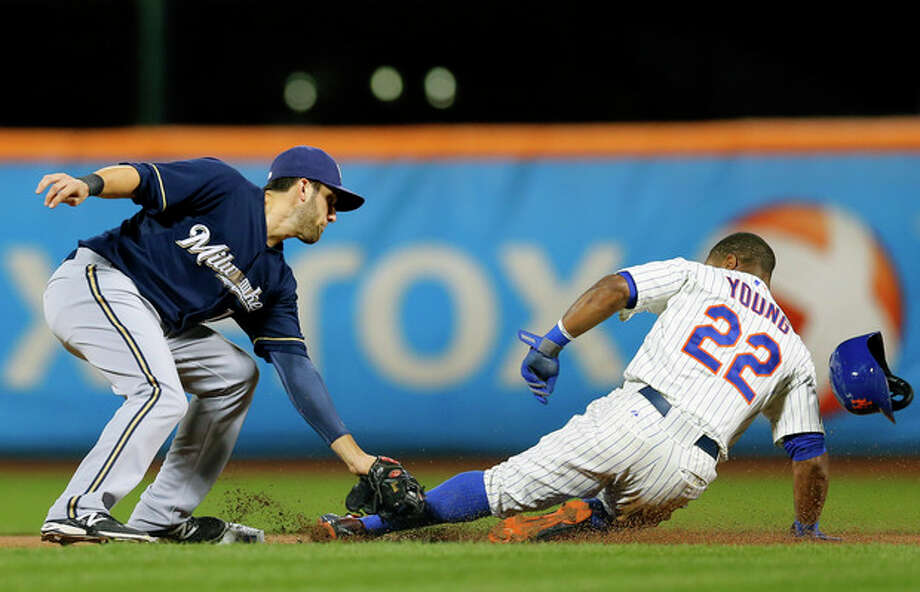 Milwaukee Brewers shortstop Jeff Bianchi (14) places the tag on the leg of New York Mets left fielder Eric Young Jr. (22) stealing second base in the first inning as it appeared Young was out, but he was called safe on the play during a baseball game at Citi Field in New York, Thursday, Sept. 26, 2013. (AP Photo/Paul J. Bereswill) / FR168017 AP