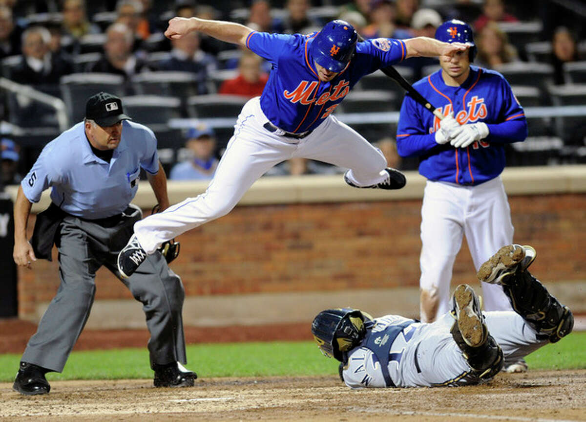 New York Mets' Daniel Murphy jumps over Milwaukee Brewers catcher Martin Maldonado attempting to score as umpire Dale Scott, left, and batter Travis d'Arnaud, right, look on during the sixth inning of a baseball game Friday, Sept. 27, 2013, in New York. Murphy was tagged out after he didn't touch the plate. (AP Photo/Bill Kostroun)