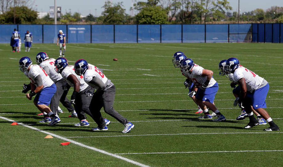 Members of the New York Giants offensive line work out during NFL football practice, Wednesday, Sept. 25, 2013, in East Rutherford, N.J. (AP Photo/Julio Cortez) / AP
