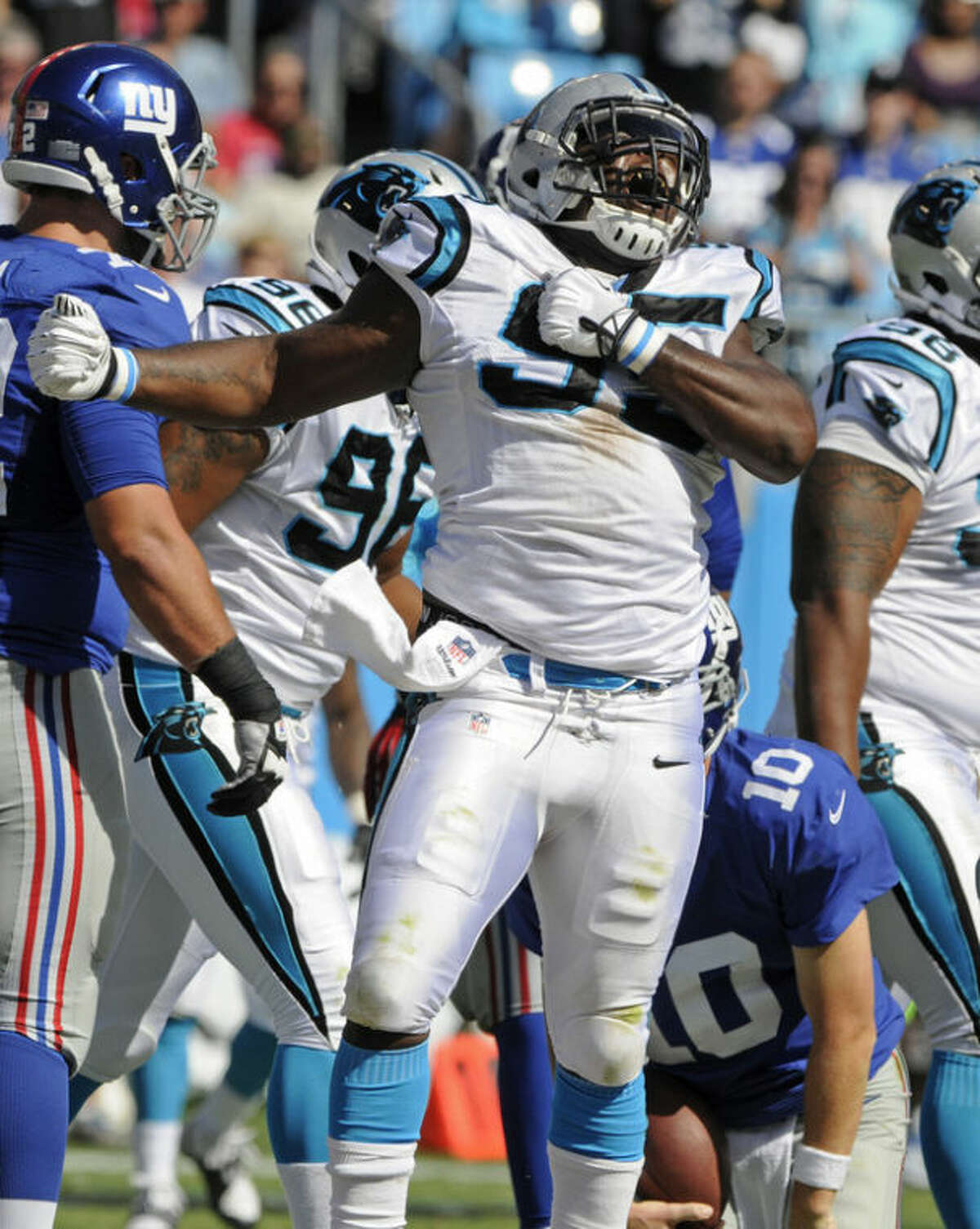 Carolina Panthers' Charles Johnson (95) reacts after sacking New York Giants quarterback Eli Manning (10) during the second half of an NFL football game in Charlotte, N.C., Sunday, Sept. 22, 2013. The Panthers won 38-0. (AP Photo/Mike McCarn)