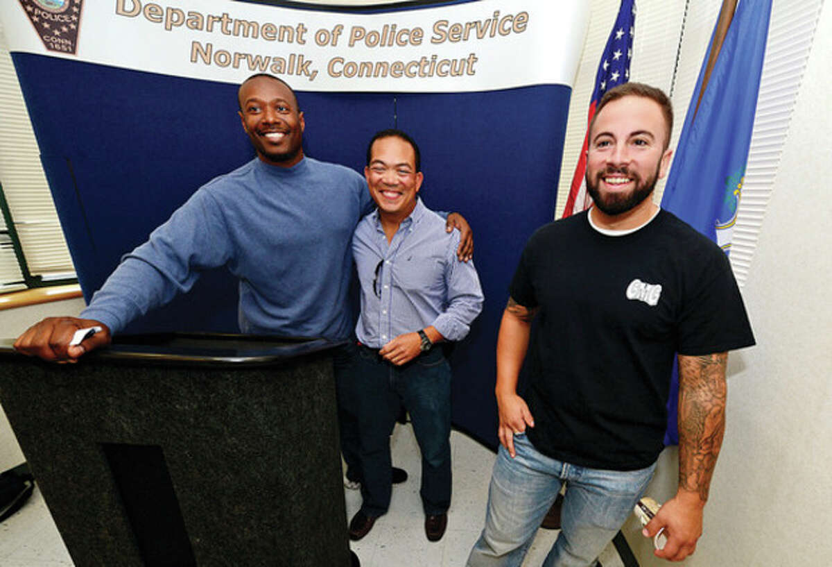 Hour photo / Erik Trautmann Norwalk Police officer Shawn Wong Won, center, and fellow officers Max Sixto and Dave Geismar at the retirement party for Won Wong at the station Friday.