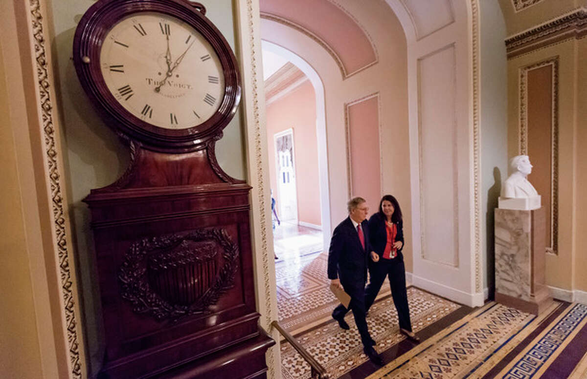 With time running out, Senate Minority Leader Mitch McConnell of Ky., walks past the Ohio Clock to the House chamber on Capitol Hill in Washington, Friday, Sept. 27, 2013, for the vote on a bill to fund the government, but stripped of the defund
