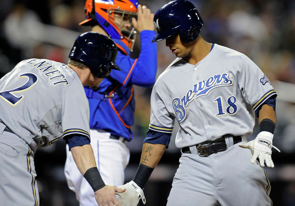 Milwaukee Brewers' Khris Davis, right, celebrates with Scooter Gennett after Davis hit a two-run home run during the first inning of a baseball game against the New York Mets Friday, Sept. 27, 2013, in New York. (AP Photo/Bill Kostroun)
