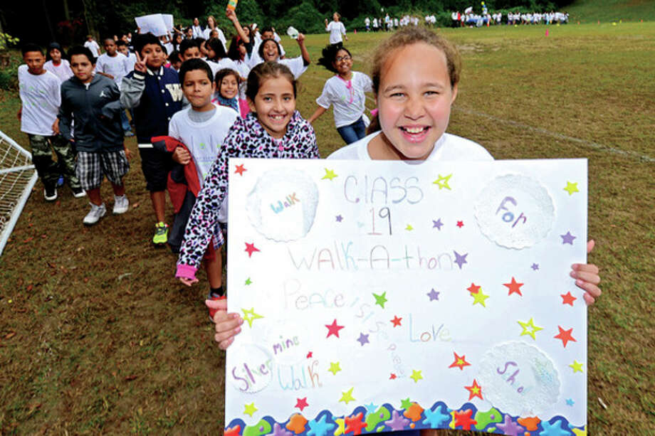 Hour photo / Erik Trautmann Silvermine Elementary School 5th grader China Tinnan leads her class as the school raised over $22,000 for PTO programs and to revamp the schools computer room during the school's walkathon Friday. / (C)2013, The Hour Newspapers, all rights reserved