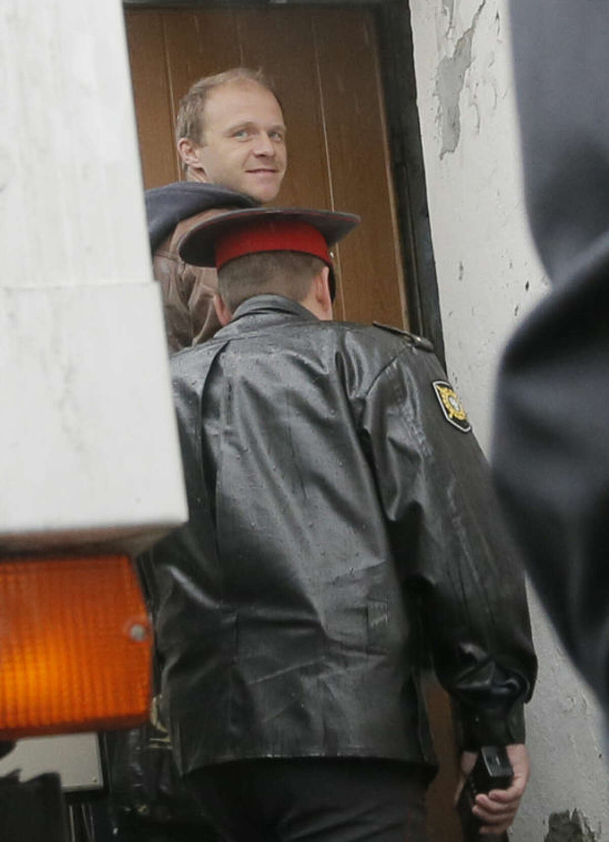 Photographer Denis Sinyakov, top, smiles as he is escorted into a court room in Murmansk, Russia, on Thursday, Sept. 26, 2013. A Russian court on Thursday jailed a photographer Denis Sinyakov, who was part of the 30-member Greenpeace team protesting near an oil platform last week. Two members of the group were detained Sept. 18 in their attempt to scale the Russian Arctic platform. The Coast Guard seized Greenpeace's ship the next day and towed it with the 30 activists aboard, to Murmansk. The activists are being investigated for piracy. (AP Photo/Efrem Lukatsky)