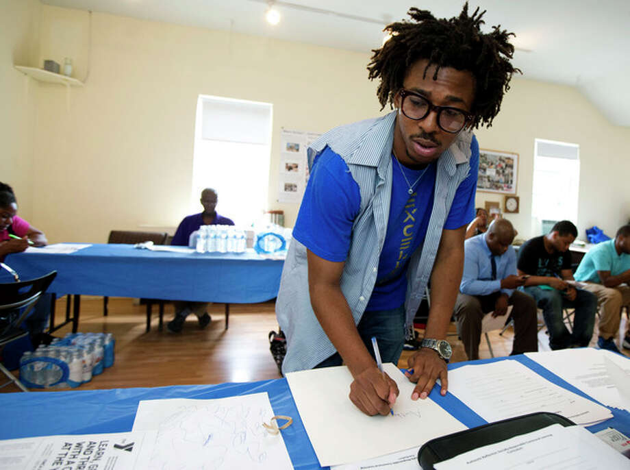 FILE - In this Wednesday, July 31, 2013, file photo, Americorps volunteer John Harris III, who is helping to coordinate a jobs fair program, fill up some documents for job seekers in Washington. The Labor Department reports on the number of Americans who applied for unemployment benefits for the third week of September on Thursday, Sept. 26, 2013. (AP Photo/Manuel Balce Ceneta, File) / AP
