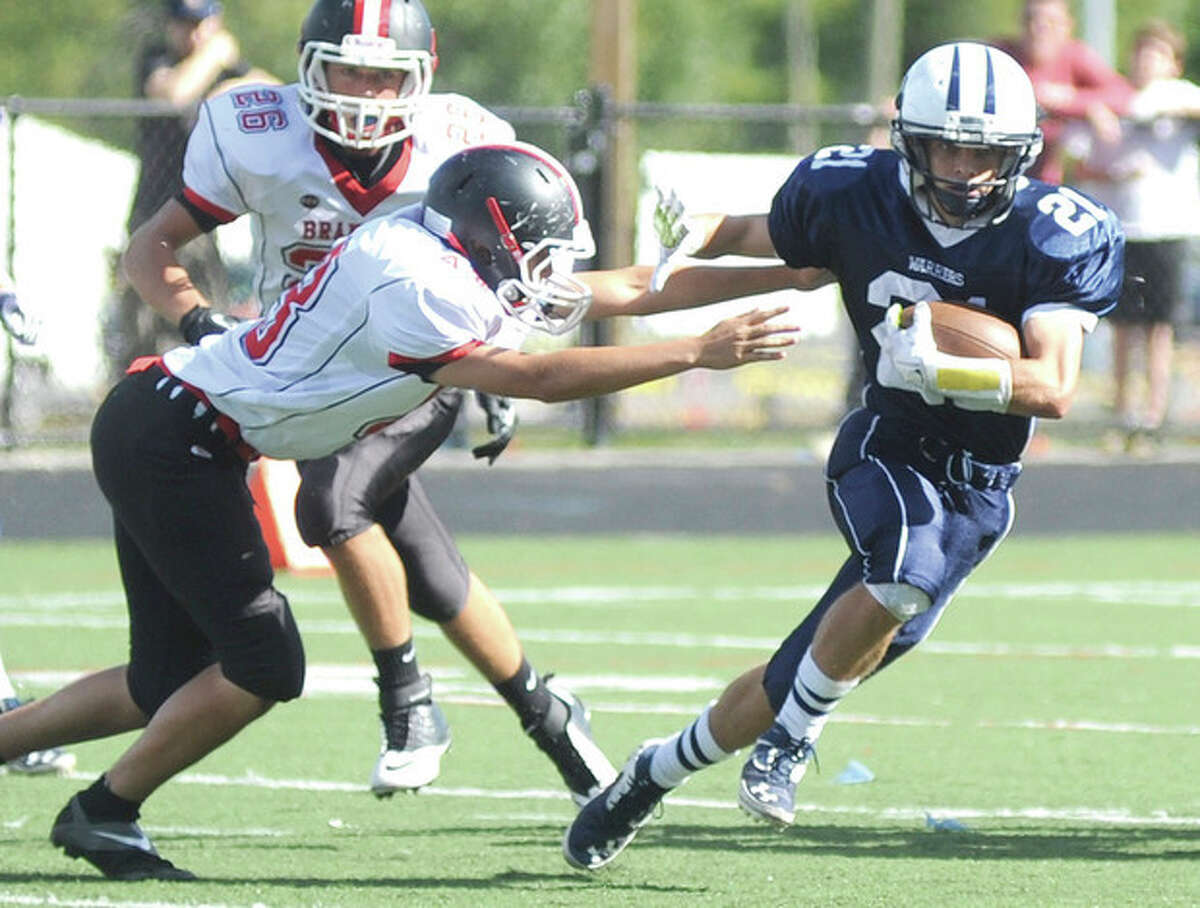 Hour photo/John Nash Wilton's Patrick Ryan, right, cuts away from Branford's Colin Tracy, front, and Noah DeGoursey during Saturday's non-conference football game at Fujitani Field in Wilton. Ryan rushed for more than 150 yards in the Warriors 35-0 win.