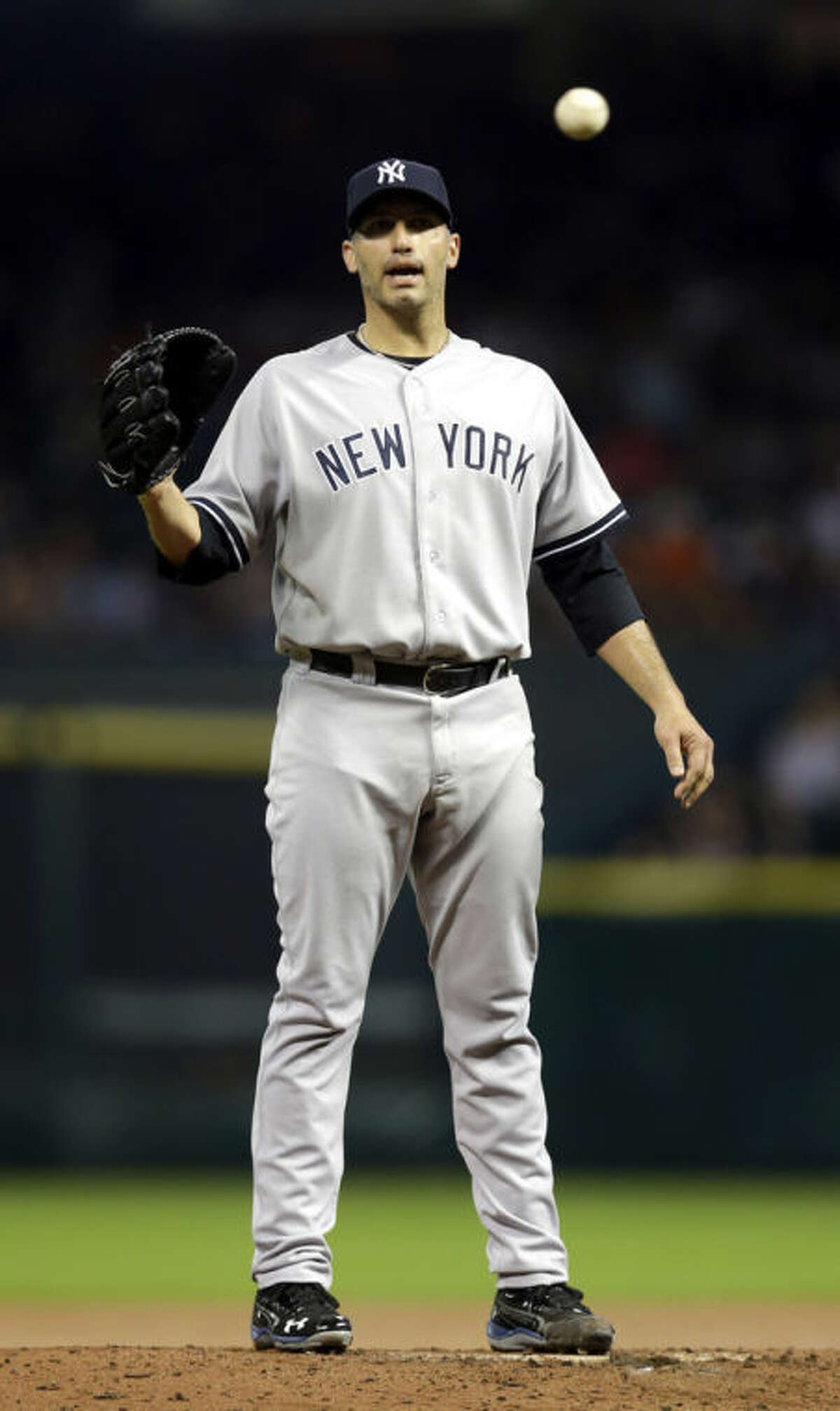 New York Yankees starting pitcher Andy Pettitte reaches for the ball after Houston Astros' Jose Altuve scored during the fourth inning of a baseball game Saturday, Sept. 28, 2013, in Houston. (AP Photo/David J. Phillip)