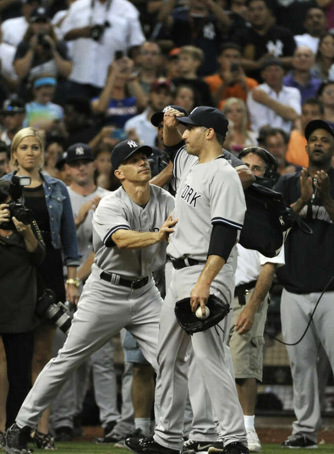 New York Yankees manager Joe Girardi, left, pushes starting pitcher Andy Pettitte back out on the field after beating the Houston Astros 2-1 for his final Major League game Saturday, Sept. 28, 2013, in Houston. Pettitte is retiring after 18 seasons. (AP Photo/Pat Sullivan)
