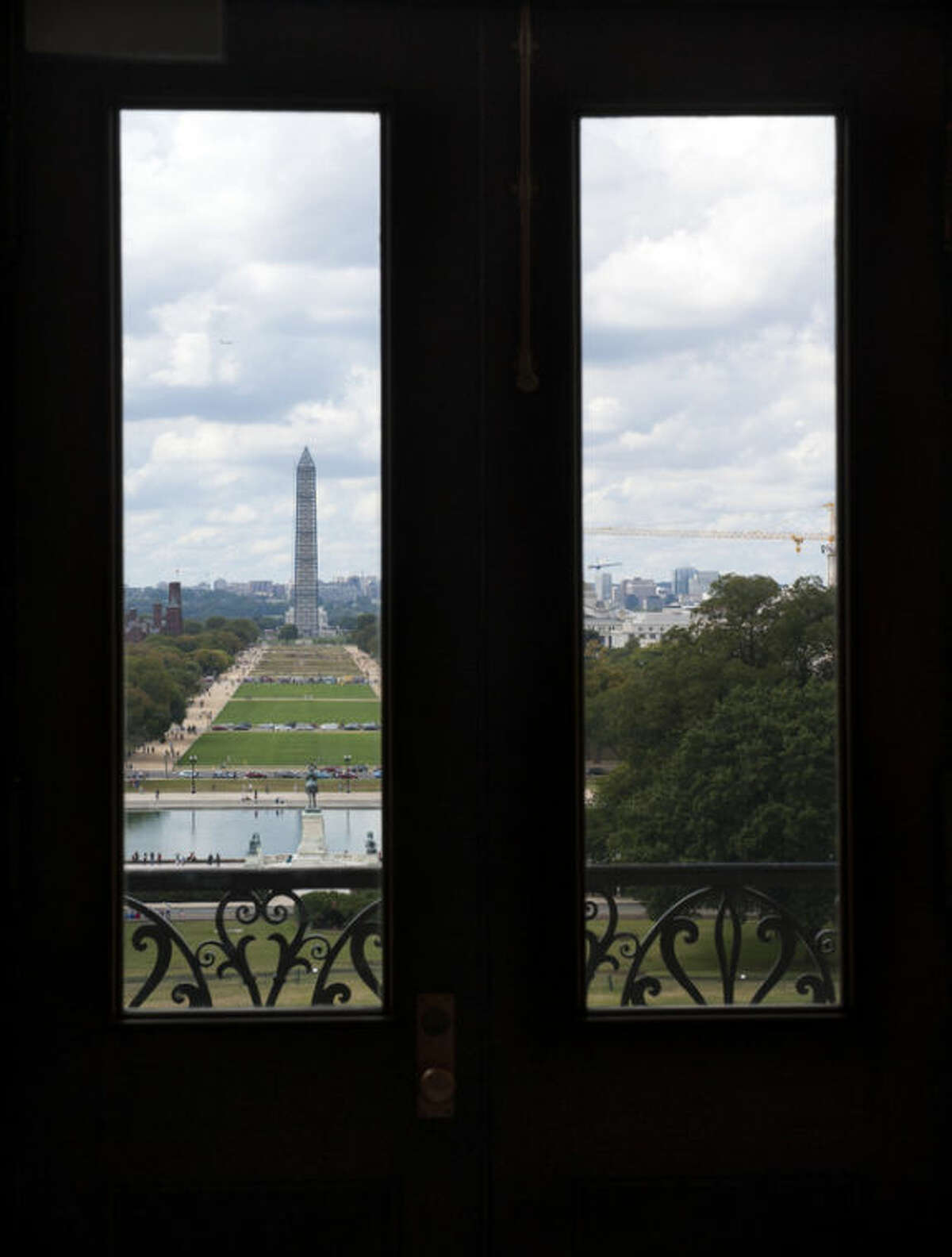 The Washington Monument is seen through windows in a door in the U.S. Capitol Sunday morning, Sept. 29, 2013, as the United States braces for a partial government shutdown Tuesday after the White House and congressional Democrats declared they would reject a bill approved by the Republican-led House to delay implementing President Barack Obama's health care reform.(AP Photo/Cliff Owen)