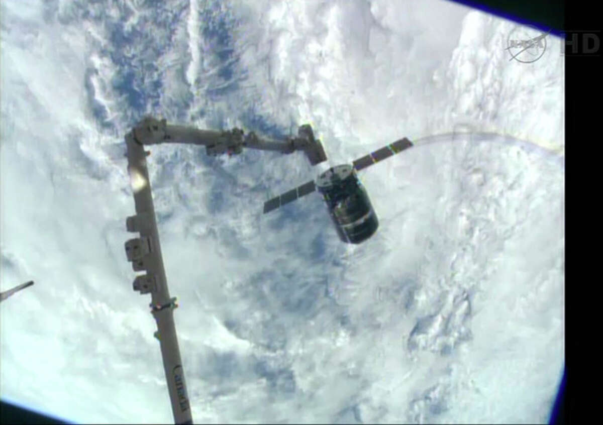 This framegrabbed image provided by NASA-TV shows the Cygnus spacecraft as it approaches the International Space Station Sunday Sept. 29, 2013. The Canadarm 2 which will grapple the spacecraft can be seen lower left. (AP Photo/NASA-TV)
