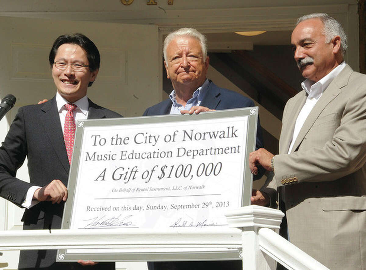 Kenneth Kuo, President/ CEO of Rental instrument, LLC with a check for 100,000 dollars Sunday for Norwalk Mayor Riichard Moccia and Norwalk Superintendent Manuel Rivera at the grand opening of the new Rental Instrument location in Norwalk. Hour photo/Matthew Vinci