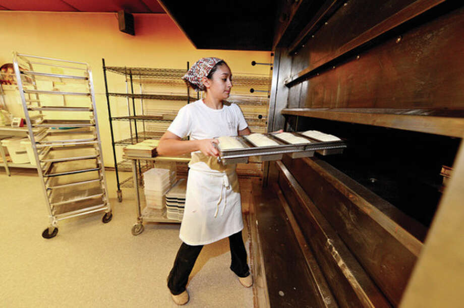 Hour photo / Erik TrautmannA fresh batch of dough is loaded into the overn's at Norwalk's Wave Hill Breads. / (C)2013, The Hour Newspapers, all rights reserved