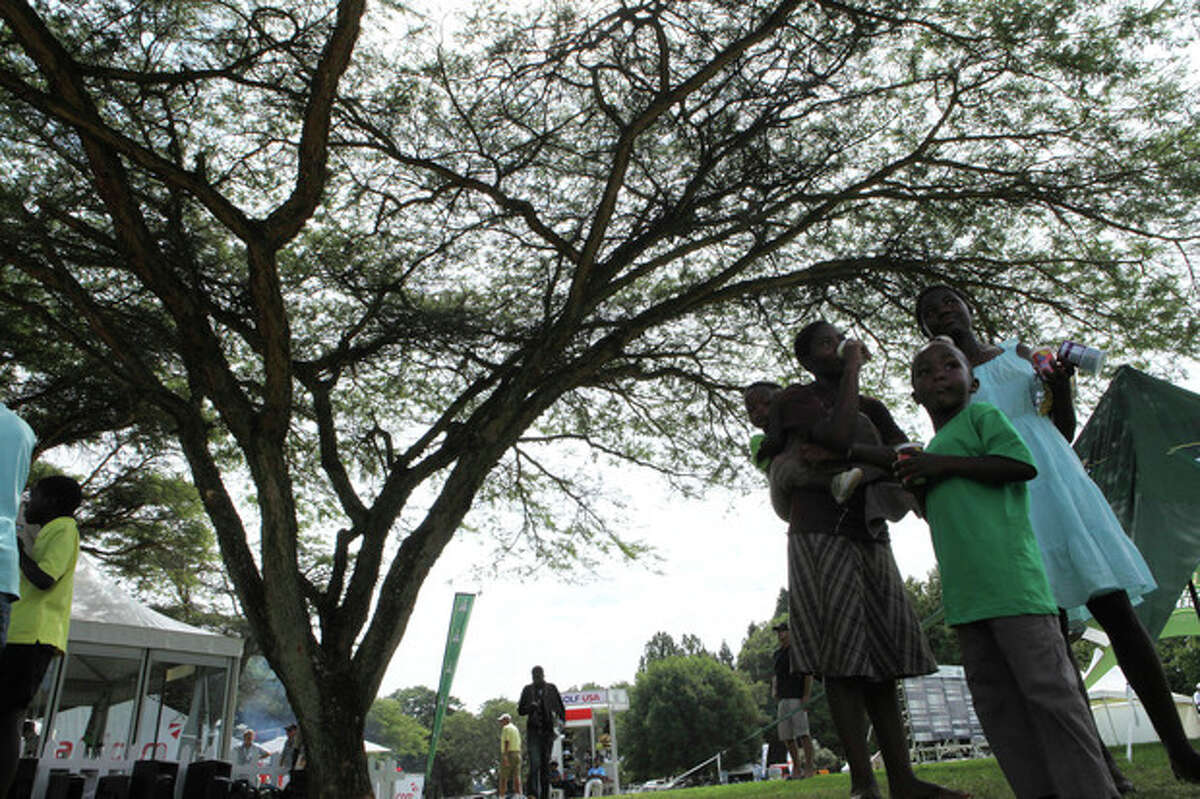 in this photo taken Tuesday, June 4, 2013, a family seeks shade beneath the indigenous msasa trees at the Royal Harare Golf Club. Indigenous trees are going to stay but