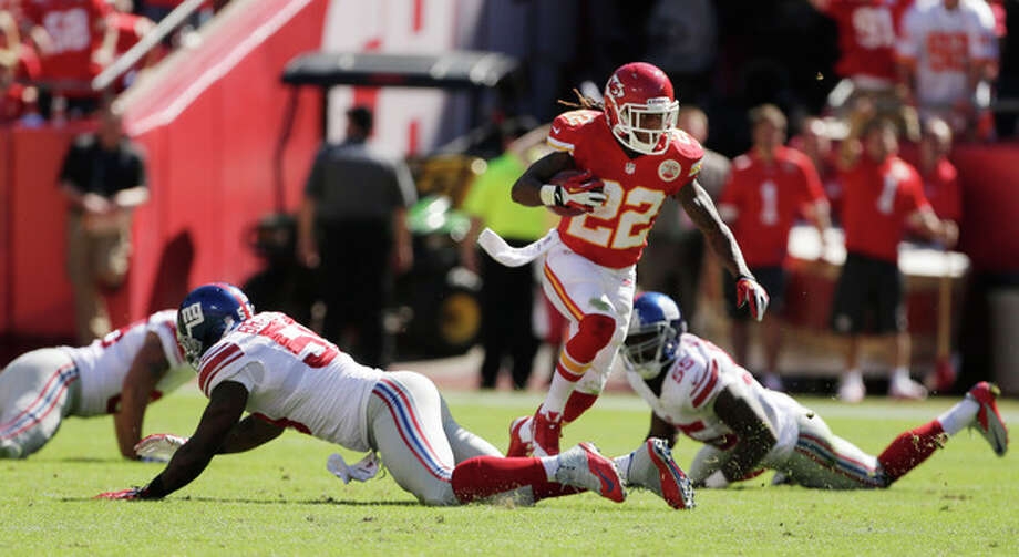 Kansas City Chiefs kick returner Dexter McCluster (22) runs through New York Giants defenders for a touchdown during the second half of an NFL football game at Arrowhead Stadium in Kansas City, Mo., Sunday, Sept. 29, 2013. (AP Photo/Charlie Riedel) / AP