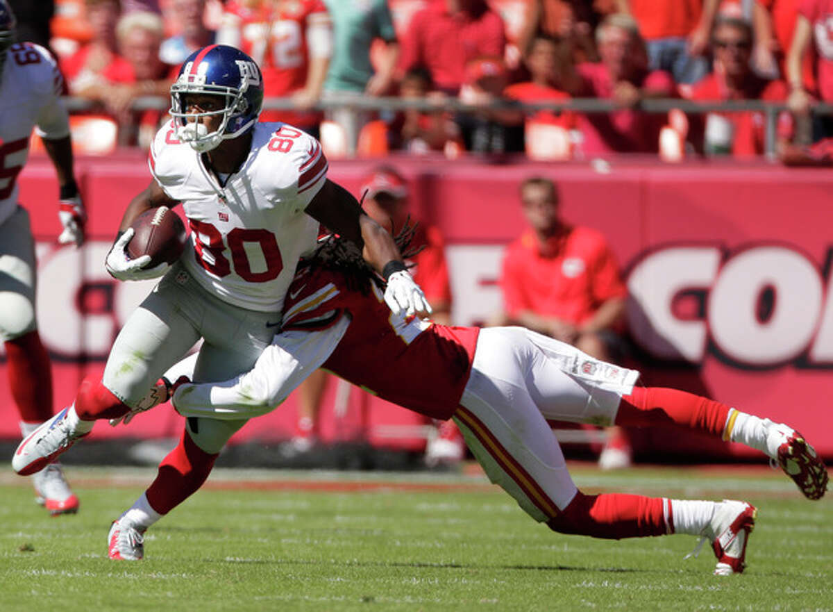 New York Giants wide receiver Victor Cruz (80) is tackled by Kansas City Chiefs cornerback Dunta Robinson (21) during the first half of an NFL football game at Arrowhead Stadium in Kansas City, Mo., Sunday, Sept. 29, 2013. (AP Photo/Charlie Riedel)