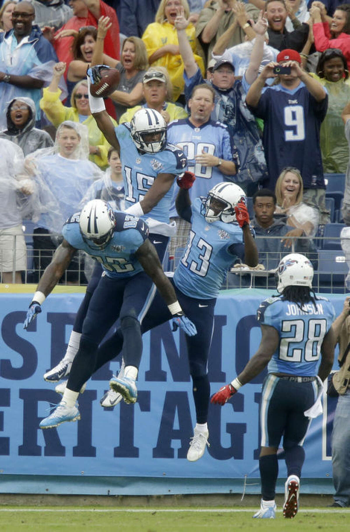 Tennessee Titans wide receiver Justin Hunter (15) celebrates with Delanie Walker (82) and Kendall Wright (13) after Hunter caught a 16-yard touchdown pass against the New York Jets in the second quarter of an NFL football game on Sunday, Sept. 29, 2013, in Nashville, Tenn. Titans running back Chris Johnson (28) runs to join in. (AP Photo/Wade Payne)