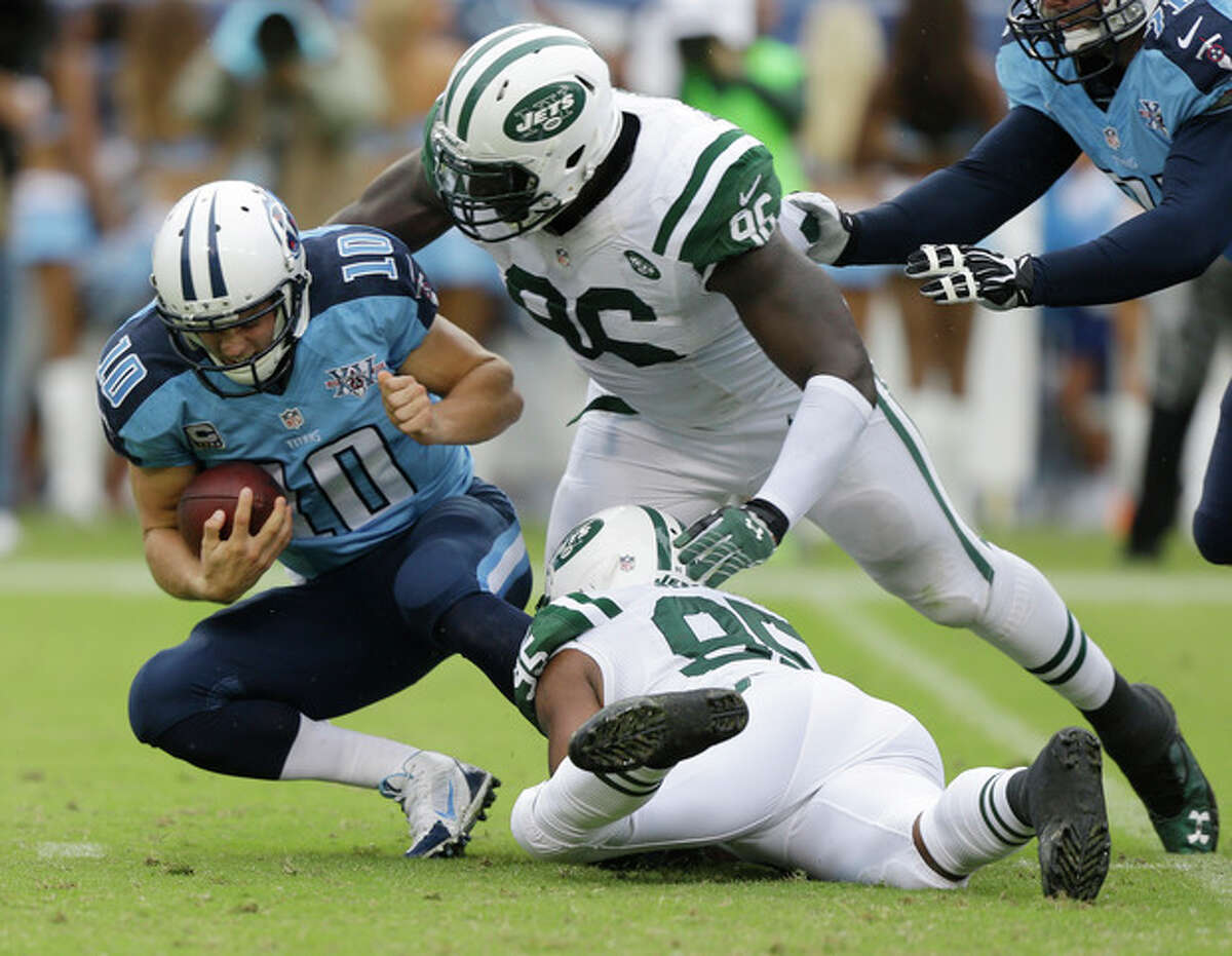 New York Jets defensive end Muhammad Wilkerson (96) and Antwan Barnes (95) bring down Tennessee Titans quarterback Jake Locker (10) in the second quarter of an NFL football game on Sunday, Sept. 29, 2013, in Nashville, Tenn. (AP Photo/Wade Payne)