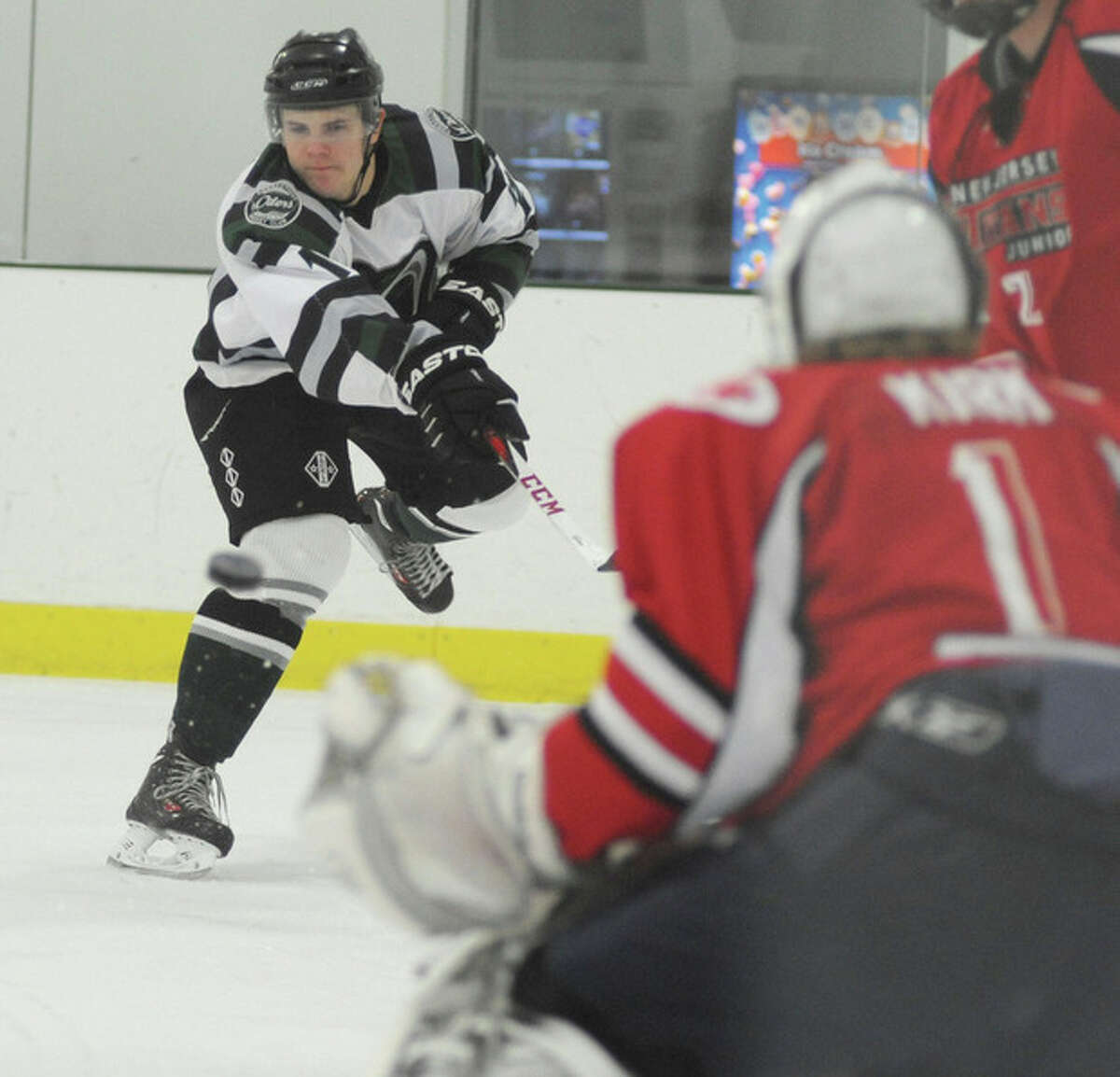Hour photo/John Nash - Connecticut Oilers forward Michael Bunn, left, fires a shot on goal and New Jersey Titans goaltender Justin Kirk during Sunday's game at the SoNo Ice House.