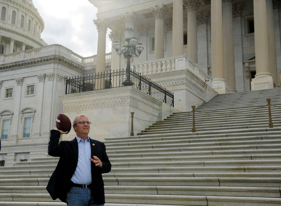 """Rep. Kevin Cramer, R-Co., throws a football while waiting for to join other Republican House Members to call on Senate Democrats to """"come back to work"""" on the Senate Steps of the U.S. Capitol Sunday, Sept. 29, 2013 as the United States braces for a partial government shutdown Tuesday after the White House and congressional Democrats declared they would reject a bill approved by the Republican-led House to delay implementing President Barack Obama's health care reform. (AP Photo/Cliff Owen) / FR170079 AP"""