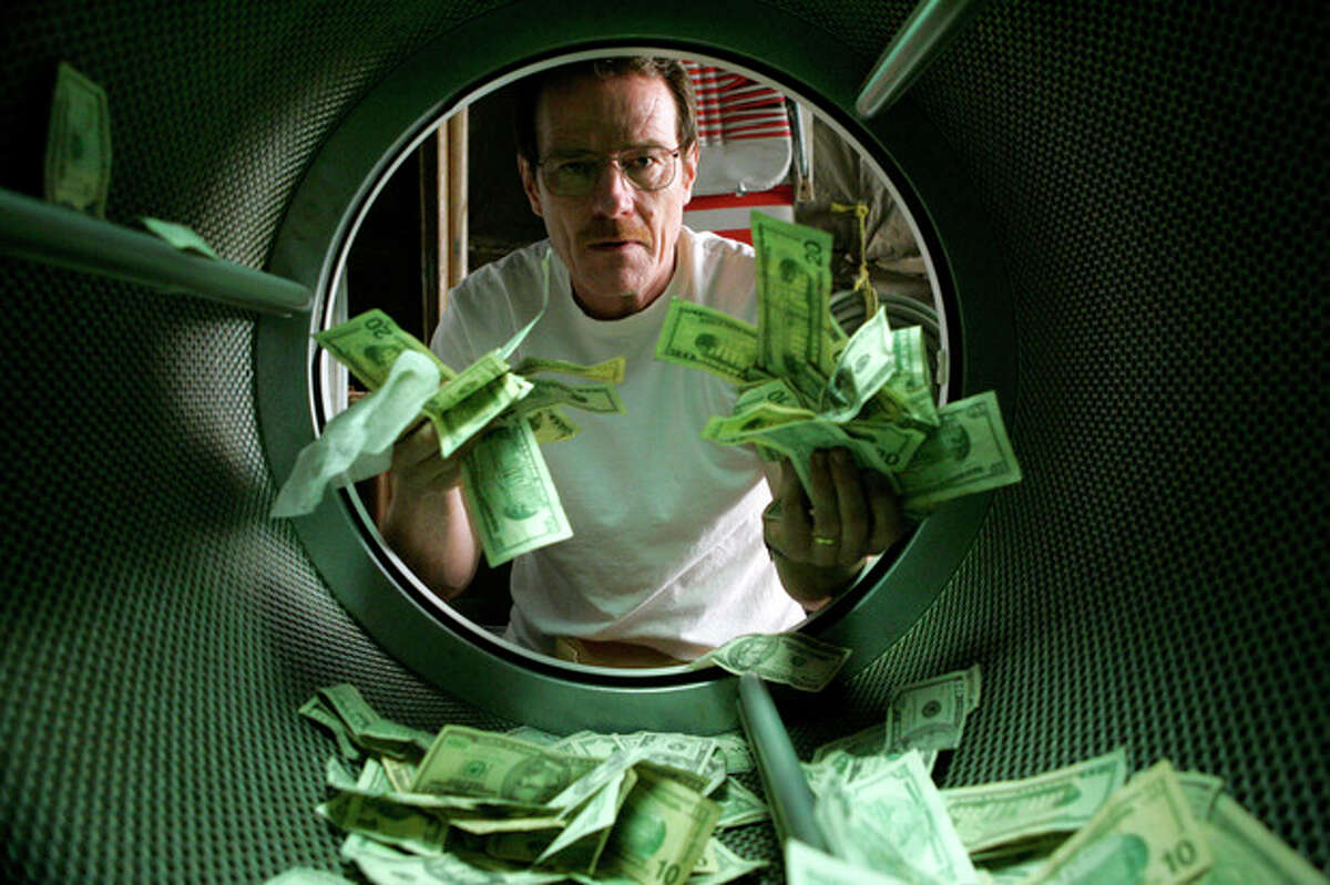This image released by AMC shows Bryan Cranston as Walter White laundering money in the pilot episode of