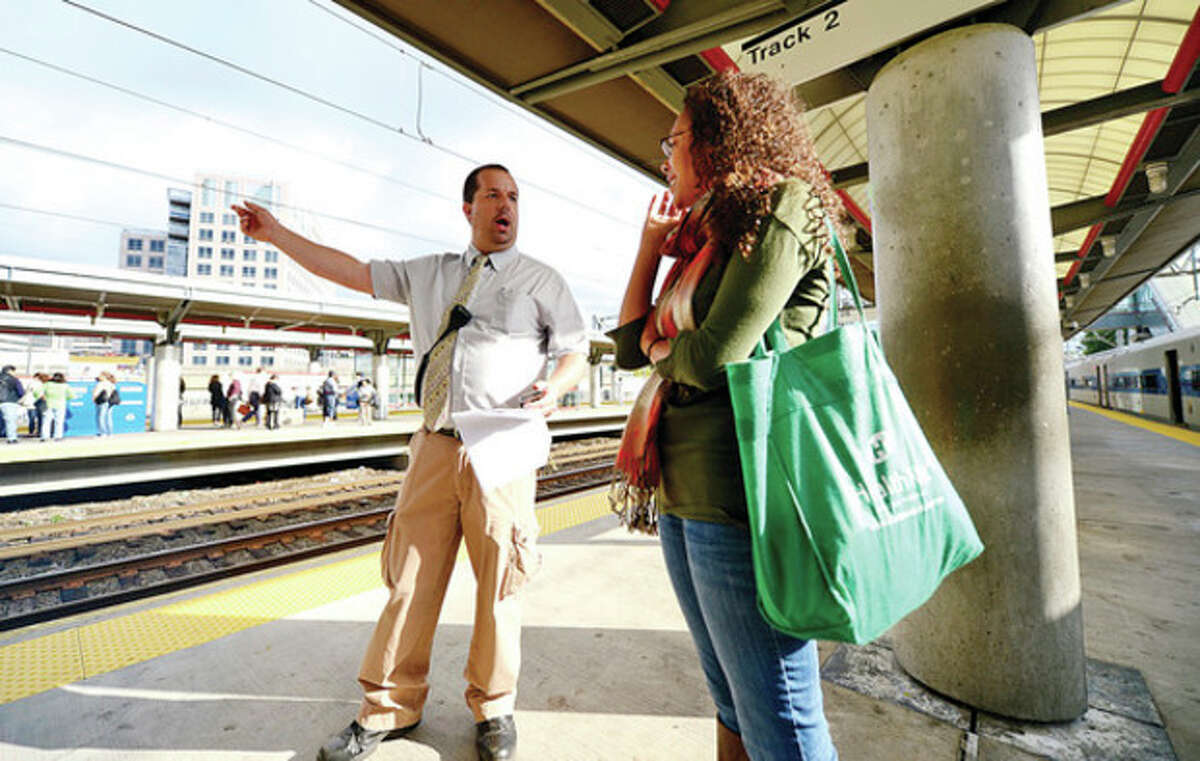 Above, Metro North passengers get to their destinations Thursday morning at the South Norwalk train station. At right, Metro North employees try to help passengers get to their destinations Thursday morning at the Stamford train station.
