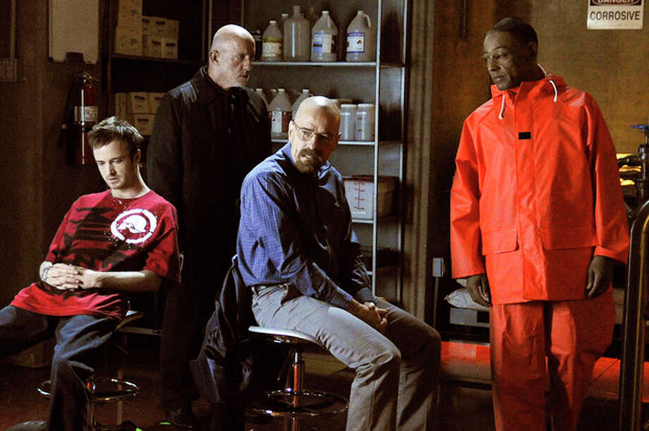 "This image released by AMC shows, from left, Jesse Pinkman, played by Aaron Paul, Mike Ehrmantraut, played by Jonathan Banks, Walter White, played by Bryan Cranston and Gustavo ""Gus"" Fring, played by Giancarlo Esposito in a scene from season four of ""Breaking Bad."" Any ""Breaking Bad "" fan could be forgiven for concluding that Sunday's finale held no major surprises. That's because this AMC drama series has delivered surprises, shock and OMG moments dependably since its premier five seasons ago. Just like it did on its final episode. (AP Photo/AMC, Ursula Coyote) / AMC"
